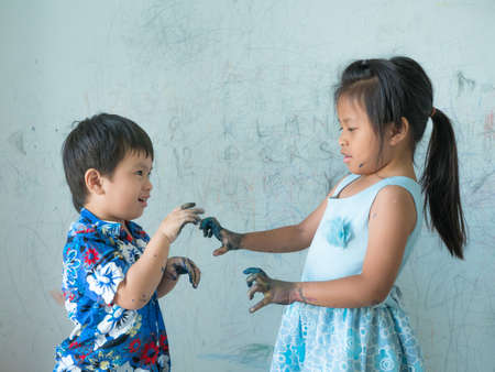 two child painting on hand and funny tease,  dirty wall background,
