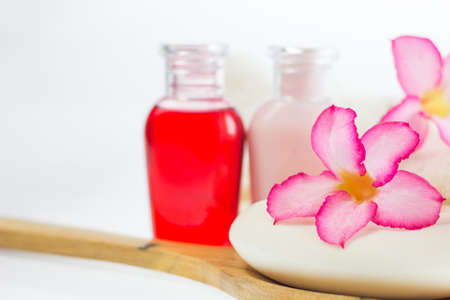 Azalea flowers on piece soap and blur liquid soap background, wooden ladle on white background,