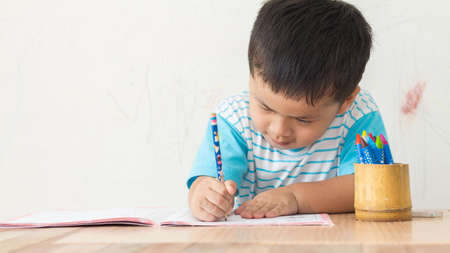 Little boy write paper on white wall, Banque d'images
