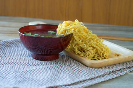 yellow Noodles on wooden bamboo tray, blurred soup cup, Stock Photo