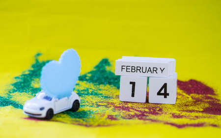 Blurred Blue heart on white toy car, Alphabet Love on yellow paper background,
