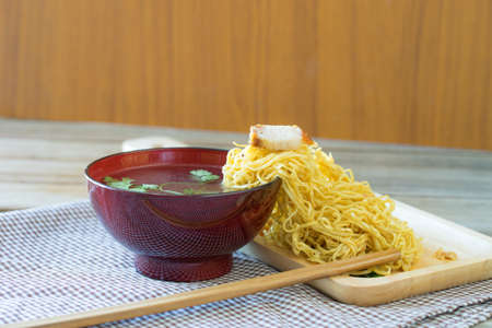 yellow Noodles on side cup soup in wooden table,