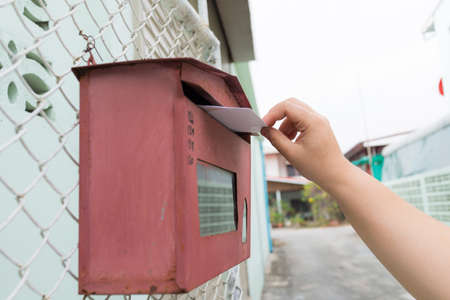 posting a letter to red british postbox on street, Closeup on a womans hand as she is posting a letter,