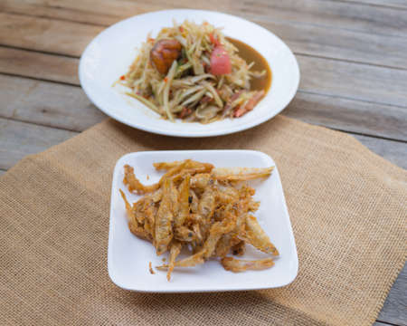 Small fried fish on blurred Papaya pok in sackcloth on table background