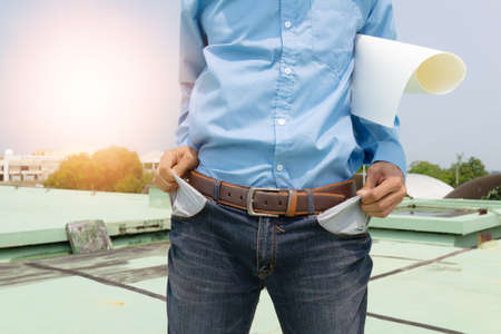 Engineer man pull the pants pocket on blurred building background,