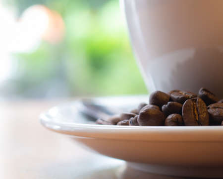 Raw coffee beans on blurred white glass and bokeh background,
