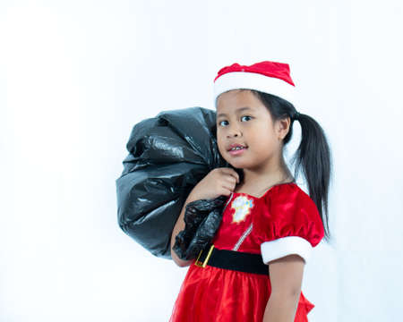 Cute Girl wearing Santa suit and holding black bag on white background,