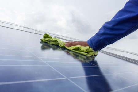 Technician holding the towel to wipe the solar cell panel