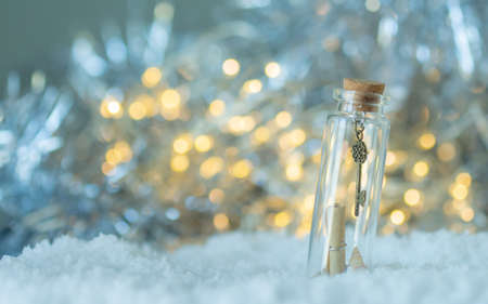 Small key in the bottle glass on the white snow with bokeh light,