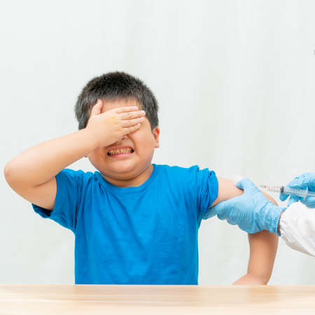 Cute a little boy is being injected and hands are closed with his own eyes on white background,