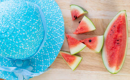 Slice watermelon and blue hat on the wooden pattern table background,