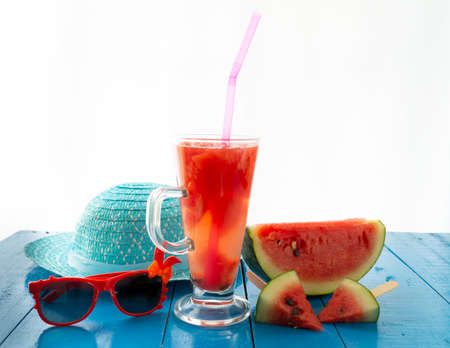 Watermelon and black glasses in the blue table on blurred blue hat background, Reklamní fotografie