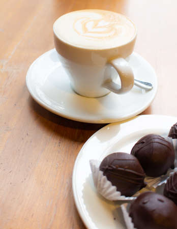 Hot late art in white cup and blurred chocolate on table,