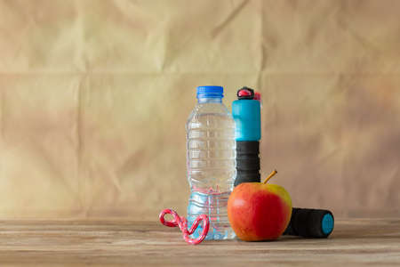 Earphone red apple and bottle water with jump robe on wooden colour background, Reklamní fotografie