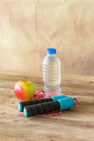 red apple and bottle water with jump robe on wooden colour background,