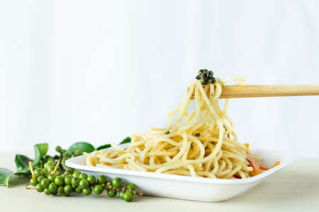 Pepper beads on spaghetti and chopsticks on white background,