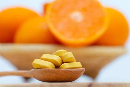 Medicine in wooden spoon on blurred orange slice  background,