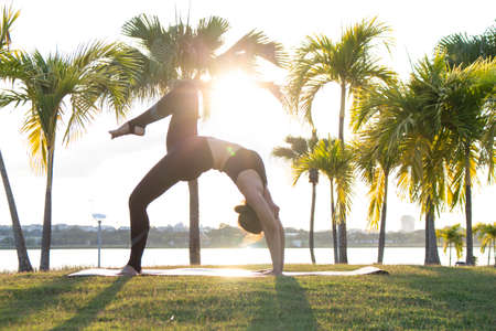 Women exercise to lift up the legs, lovely girl playing a yoga in the garden on light a sun background, Reklamní fotografie