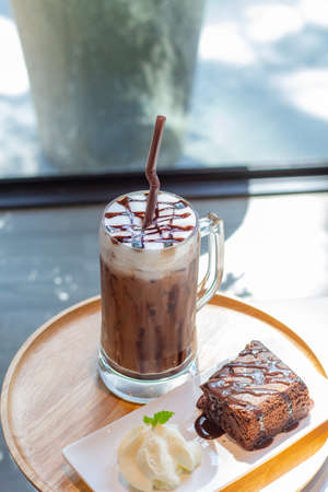 Ice coffee a late art in the glass on the table background, chockolate cake in wooden tray, Reklamní fotografie