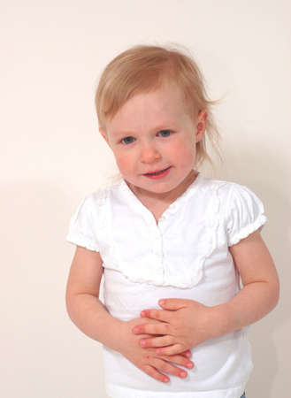 A girl preschooler with her hands on her stomach photo