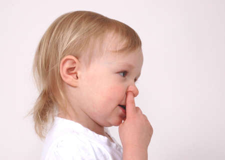 Little girl picks her nose during a photo shoot photo