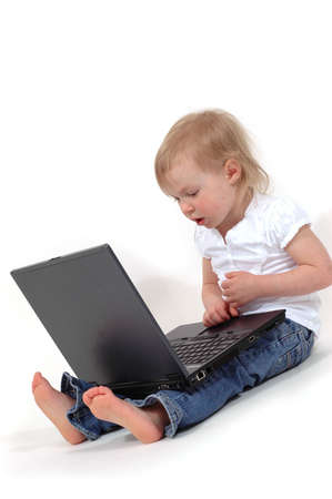 A little girl playing with a laptop computer photo