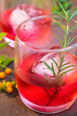 refreshment: Glasses of refreshment raspberry flavor fizz with ice and rosemary on wood table decorated with berry and leaf