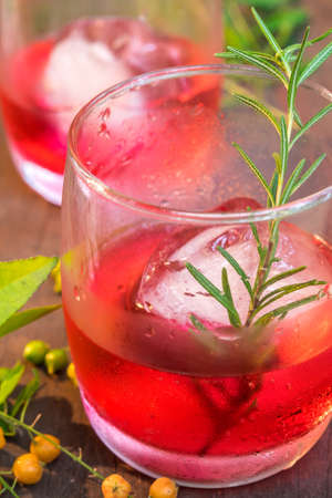fizz: Glasses of refreshment raspberry flavor fizz with ice and rosemary on wood table decorated with berry and leaf