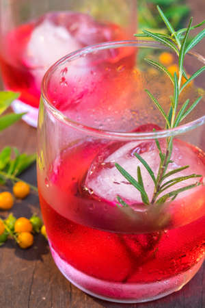 refreshment: Glasses of refreshment raspberry flavour fizz with ice and rosemary on wood table decorated with berry and leaf