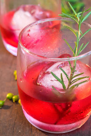 fizz: Glasses of refreshment raspberry flavour fizz with ice and rosemary on wood table decorated with berry and leaf