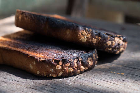 the place is outdoor: Crispy and Crunchy Over Burned Toasts place outdoor on wooden stool in Daylight