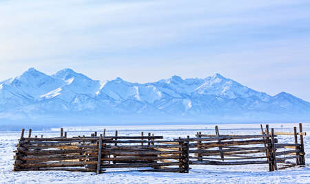 Wooden corral for cattle on the background of snow-covered mountains