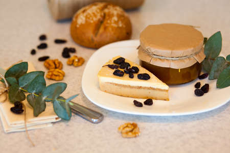 circassian: Sweet apricot jam in the glass jar and piece of tasty cake with raisins are on the plate. Knife, rose leaves and Circassian walnuts are on the table Stock Photo