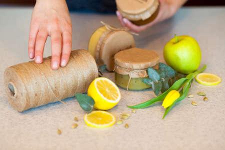 여자의 손을 신선한 레몬, 달콤한 녹색 사과와 스레드의 스풀에 둘러싸인 세 맛있는 과일 잼 중 하나 들고있다