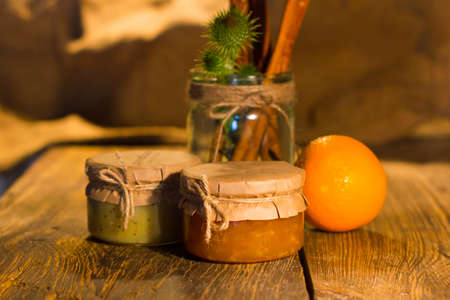 glass jars: Delicious banana and orange jam in two little glass jars with orange near them are on the wooden table