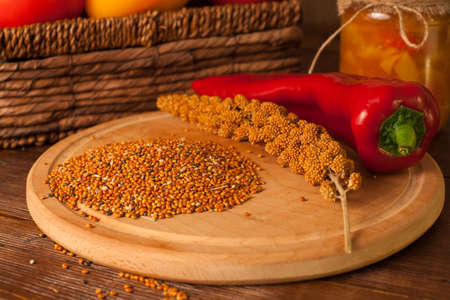 On a round plank are grains and chili on the table