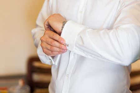 cuffs: Bridegroom buttoning cuffs on his white wedding shirt