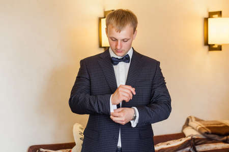 cuffs: Groom wearing blue wedding suit and buttoning cuffs