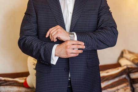 cuffs: Bridegroom wearing blue wedding suit and buttoning cuffs