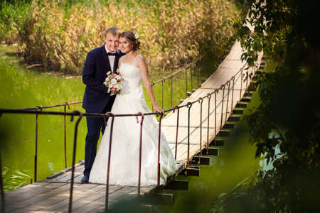 Male and female in wedding dresses on wooden bridge