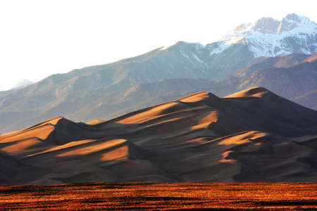 Sunset on Golden Great Sand Dunes with the background of snowcap on top of the mountain photo