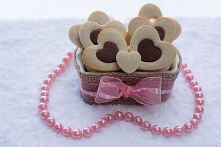 Pretty Rolled Chocolate Heart inside Vanilla Heart Sugar Cookies in a Ceramic bowl wraps with Burlap Banque d'images