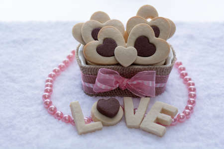 Pretty Rolled Chocolate Heart inside Vanilla Heart Sugar Cookies in a Ceramic bowl wraps with Burlap with the word \\\\\\\