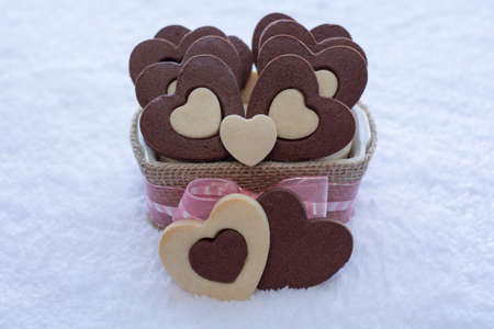 Pretty Rolled Vanilla and Chocolate Heart Sugar Cookies in a Ceramic bowl wraps with Burlap with the white rug background