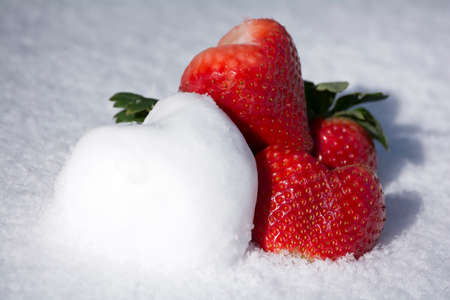 Lovely strawberries and snow heart shape on white snow background