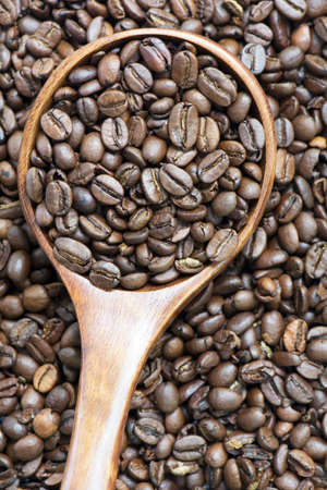 medium group of object: Medium roasted whole coffee bean in wooden spoon on coffee bean background