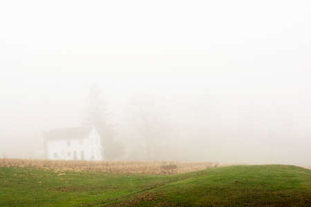 foggy hill: Small green grass hill with a blur farm house in a foggy morning background Stock Photo