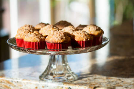 cakestand: Sunlight shining banana muffins with brown sugar topping in red paper cup on clear glass cakestand on kitchen granite countertop Stock Photo