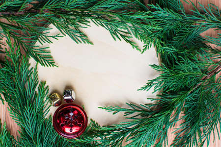 jingle bells: christmas jingle bells on hard wood space background with green leaves circle frame