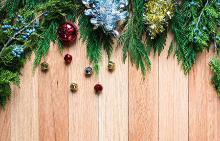 wood floor background: christmas jingle bells on hard wood floor background with green leaves top frame Stock Photo
